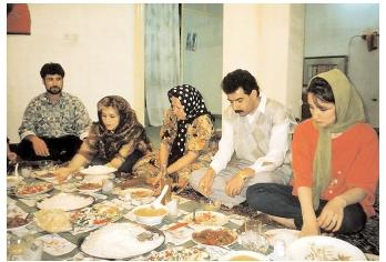 What and how people eat is determined by a variety of factors, including economic circumstances, cultural norms, and religious restrictions. Here, an Iranian family sits on the floor and eats from a cloth laden with regional delicacies. [Photograph by Earl and Nazima Kowall. Corbis. Reproduced by permission.]
